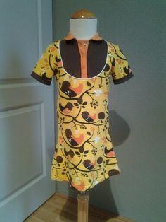 Jurkje van gele vogeltjes jersey van Majapuu uit Finland. Gecombineerd met bruine en oranje bio jersey. Afgewerkt met wit paspelband en oranje drukknoopjes.