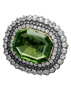 PERIDOT AND DIAMOND BROOCH An impressive Napoleon III brooch, the principal stone a 37.5 ct peridot surrounded by three graduating rows of old-cut diamonds weighing a total of 13.5 cts (approx), set in silver on gold. Circa 1890, with French import marks.