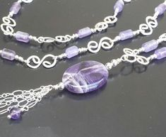 The focal point of this Y shaped necklace is the oval central pendant bead of chevron amethyst which has white inclusions mixed with the purple amethyst that gives it an interesting pattern of white and lavender veins in the deep purple stone. Five strands of silver chain fringe dangle