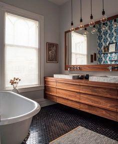 Neste banheiro o piso de ladrilhos hexagonais preto é usado para quebrar a claridade do ambiente, que possui paredes brancas e uma ampla janela. As pias, assim como a bancada e o espelho, possuem design geométrico. Já a parede refletida pelo espelho, é coberta por azulejos portugueses e dá um toque artesanal ao ambiente. Outro estilo presente é o industrial, representado pelas luminárias de vidro. #mostrablack #arte #art #arquitetura #architecture #original #conceito #contraste #harmonia…