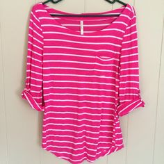 Pink 3/4 length top with white stripes Pink top with white stripes and 3/4 sleeves. Sleeves have button detail and do not roll out to full length. Pocket detail. Purchased from an online boutique. Size large. Tops