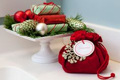 Wrap bars of soap with holiday papers and stack them on a small cake stand alongside holiday greens and ornaments