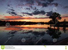 Photo about A beautifully spectacular sunset on Lake Mead in Southwest Kansas with crystal reflection of silhouetted trees and sparse clouds. Image of water, shadow, fading - 79511746 Lake Mead, Tree Silhouette, Clouds, Stock Photos, Mountains, Sunset, Water, Travel, Image