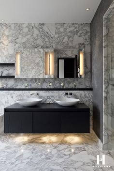 Bathrom by designer Kelly Hoppen. LIghting under floating cabinet, wood shelf and wall set-backs. resibids.com #Marble