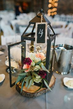 Black metal lantern wedding reception centerpiece with white spray roses, peach roses, burgundy scabiosa, seeded eucalyptus designed by Bloomtastic in Columbus, Ohio