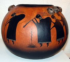Ancient hump-backed flute players - also known as Kokopelli surround the pot. Small painted gourds are attached as they carry the pots on their heads as in the ancient ways. Artist Robert Rivera.