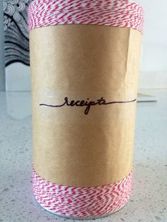 Receipt holder made by covering a tin with brown paper bag and baker's twine.