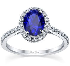 Blue sapphire engagement ring with oval cut center and pave accented band.