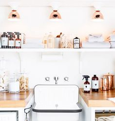 Bucket sinks, wooden tops, white shelving, rose gold lamp and container accents