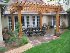 Grass Garden and Soft Brown Wood Pergola Above Several Grey Colored Chairs