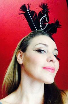 Acessório de cabeça. Tiara com aplicação de penas e fivela de metal, ornamento com cristais. Modelo Mariana Agnelli.