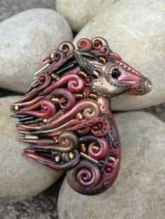 Tribal warrior horse head pendant in black, deep red and copper polymer clay. $40.00, via Etsy.