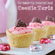 Strawberry Cheesecake Cookie Tarts - Just in time for Valentine's Day, you will fall in love with these cute little edible bowls filled with a strawberry cheesecake-like cream and topped with an adorable chocolate/strawberry swirl candy heart!