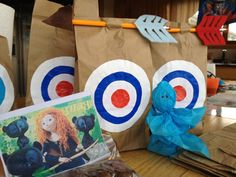 Disney's Brave birthday gift bags. Tootsie roll pop covered with tissue paper to look like wisps, blue glow sticks and chocolate teddy Graham's. with pencil arrows