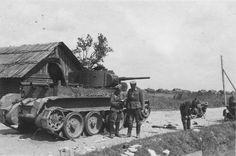 German officers standing near an abandoned Soviet BT-5 light tank in 1941.