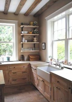Look at this rustic kitchen with the farmhouse sink-wood cabinets-lots of light and really simple-no upper cabinets just a few open shelves-really like it how bout you? by Tammy Lynn Labrake