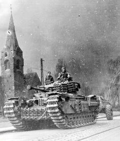 The crew of a Churchill tank gaze at the camera as their pass a church steeple with smoke rising in their wake, Western Europe, Ww2 Pictures, Military Pictures, Surplus Militaire, Vietnam, War Photography, Ww2 Tanks, Battle Tank, Panzer, British Army