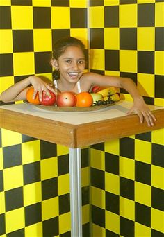 "Image: An Indian girl looks at her vanished lower body through an optical illusion while participating in an exhibit named ""A Head on a Plat..."