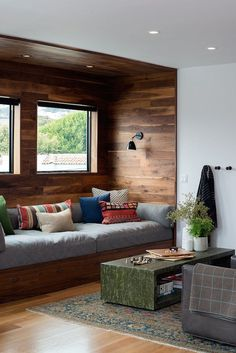 Cozy modern cabin design style. Love the wood walls and plaid blanket with those pops of green.
