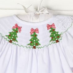 Solid white fabric with three smocked Christmas trees. The white fabric allows the smocked to really pop. Perfect for Christmas time!
