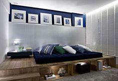 Com um layout pouco convencional, a cama fica sobre um tablado de madeira de demolição, que também forma nichos. O azul marinho é uma cor masculina e faz uma bonita composição com o branco e a madeira. Foto: site Casa.: