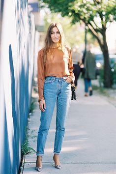 Street style com look básico de blusa marrom, mom jeans claro e scarpin estampado
