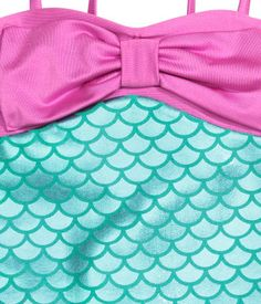 Swimsuit with a shimmering metallic pattern. Narrow shoulder straps and bow at front. Lined at top and at gusset.