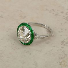 4.50ct Diamond Engagement Ring with by EstateDiamondJewelry, $76500.00  A stunning 100 year old diamond engagement ring with emerald halo set within a beautiful platinum setting. The center diamond is a K color, VS2 clarity and approx 4.50ct, and sits within an alluring halo of french-cut emeralds. The setting is handmade platinum. The Old European diamond dates back to the 1930's, and the platinum mounting was recreated in classic Art-Deco style. Another DREAM RING!