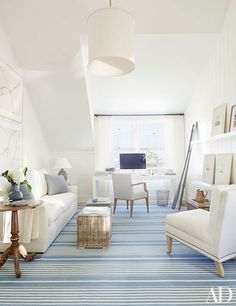 The master suite's inviting sitting area extends the home's palette of pale neutrals accented by hits of blue.