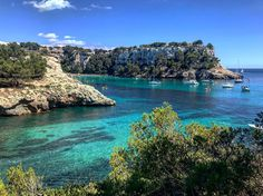 A view of the entrance to Cala galdana from the cliff path.  #calagaldana #menorca #baleares #spain  #greatbeach #bluesky #clearwater #cliffs #trees  #blueskyday  #camidecavalls #cliffwalk #picoftheday #iphone7