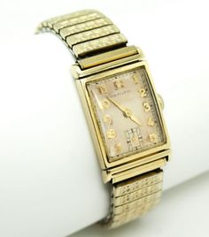 Vintage 1940s-50s Hamilton 14K Gold Award Presentation Wristwatch 19J Original Case. This is a handsome vintage Hamilton 'Award' wristwatch. The watch features a sleek 14k gold case, gold numerals and hands, and a cream dial.