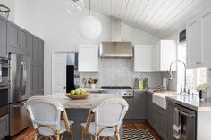 Under a sloped shiplap ceiling, this gorgeous white and gray kitchen features Serena & Lily Riviera Counter Stools placed in front of a gray island finished with a White Macaubas Quartzite countertop lit by both a white glass globe pendant and a clear glass globe pendant.