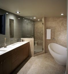Classic travertine with modern class tile wall that runs through and into the shower area.