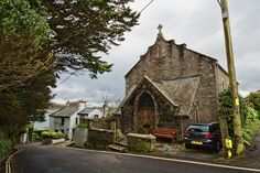Pretty church and cottages line hilly streets in the village of Saint Mawes, Cornwall, England