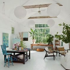 Beautiful and inspiring home art studio ideas...love the all white walls and ceiling, dark furniture, beams, plants and huge window.  Ideas for my garage studio!