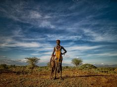 "Under African Skies  Photograph by Carey Nash  A Hamar woman and her son stand beneath a dramatic sky in Ethiopia's Omo Valley. ""After walking from our tent along the riverbed, we met up with this nearby village and the beautiful people [who] lived there,"" writes photographer Carey Nash. ""We felt so welcomed."""