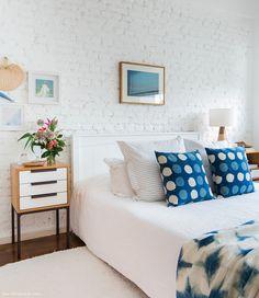 Quarto de casal tem parede de tijolinho branca, criado mudo e almofadas estampadas azul índigo.