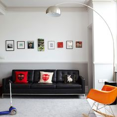 A row of small paintings hung above the sofa creates a unique take on the feature wall.