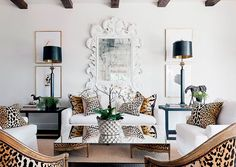 Leopard print velvet pillows and chair backs add a luxurious, exotic feel to this glamorous black and white traditional living room.