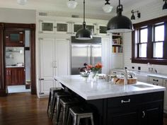 What a dream space. Designer Rebekah Zaveloff mixed traditional-style cabinets with industrial-style light fixtures and barstools at the kitchen's sleek black island to create a look that's an instant classic.