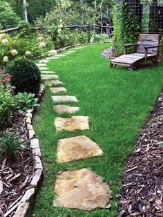 New A stone pathway invites visitors to stroll along the flower beds in this cottage garden Rustic seating and fencing plete the look in this backyard