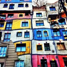 """Welcome to another edition of #ArtThursday! The Hundertwasserhaus, an apartment complex in Vienna, embodies Austrian painter, architect and sculptor Friedensreich Hundertwasser's passionate rejection of the straight line. In his lifetime, he went so far as to call straight lines """"godless and immoral."""" Built between 1983 and 1985 alongside architects Joseph Krawina and Peter Pelikan, Hundertwasserhaus has undulating floors, a grass-covered roof and 250 trees growing inside the rooms, their…"""