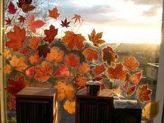 Getrocknete Blätter auf die Klebseite von Bucheinschlagfolie legen, Folie um die Blattränder herum abschneiden, so dass noch genug Rand zum Kleben auf der Fensterscheibe übersteht.
