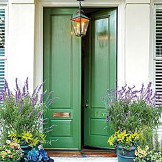 Green to Envy | Give guests a warm welcome with friendly tones of green, gray, and blue. This grand double-door entry is balanced by its easygoing, leafy hue and simple carving. The weathered patina of the pendant lantern suggests a home that's mellowed over time.