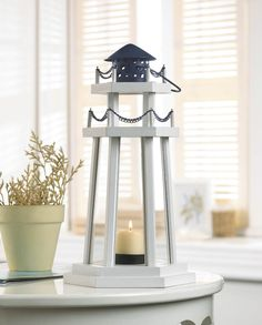 Shine a light into the night with this absolutely charming wooden candle lantern. A classic lighthouse framework is painted white and fitted with slender glass panels and topped with black metal embel
