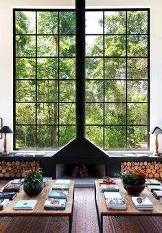 Ventanal fijo con chimenea salón igual ventanal a los lados con puertas todo madera                                                                                                                                                      Más