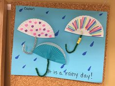 Rainy day? No problem! Make colorful umbrella art indoors using muffin liners or coffee filters.   Materials Needed:   Muffin liners or coffee filters (or both!), blue construction paper, white crayons, glue.  Show children how to poke one end of a chenille stem through the center of the fold. Curl the other end of the stem to make a handle. Click image for more ideas!