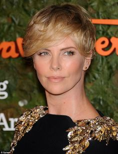 Charlize Theron cuts a willowy figure in a black gown with gold embellished shoulders at star-studded bash