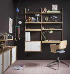 A home office with a wall-mounted shelving unit in bamboo with desk, combined with white sliding doors. Shown together with a swivel chair in oak veneer with a grey wool seat.