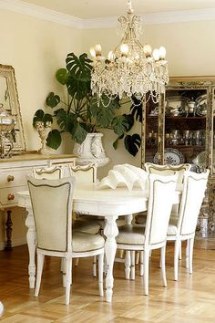 Elegant dining room in white.  Pretty chairs, table, chandelier.